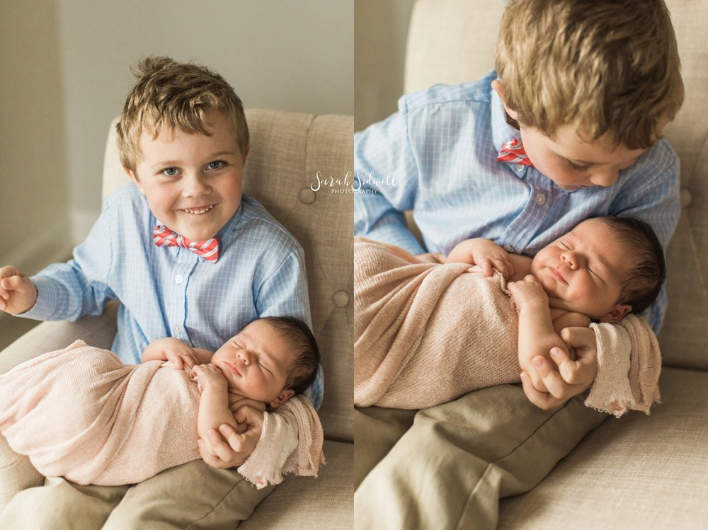 A little boy holds his new sister.