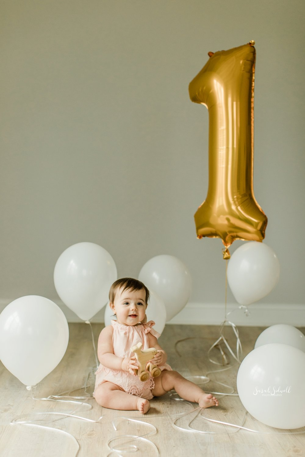 A baby plays with a number 1 balloon | Nashville Baby Photographer