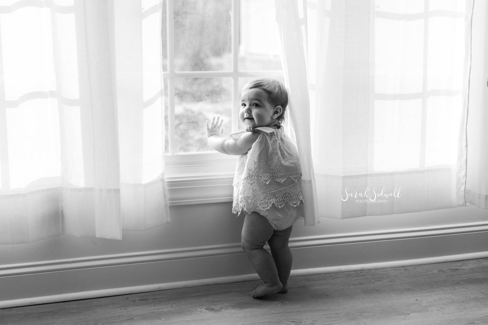 A baby stands by a window | Nashville Baby Photographer