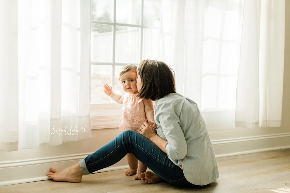 A mother sits by a window with her baby.