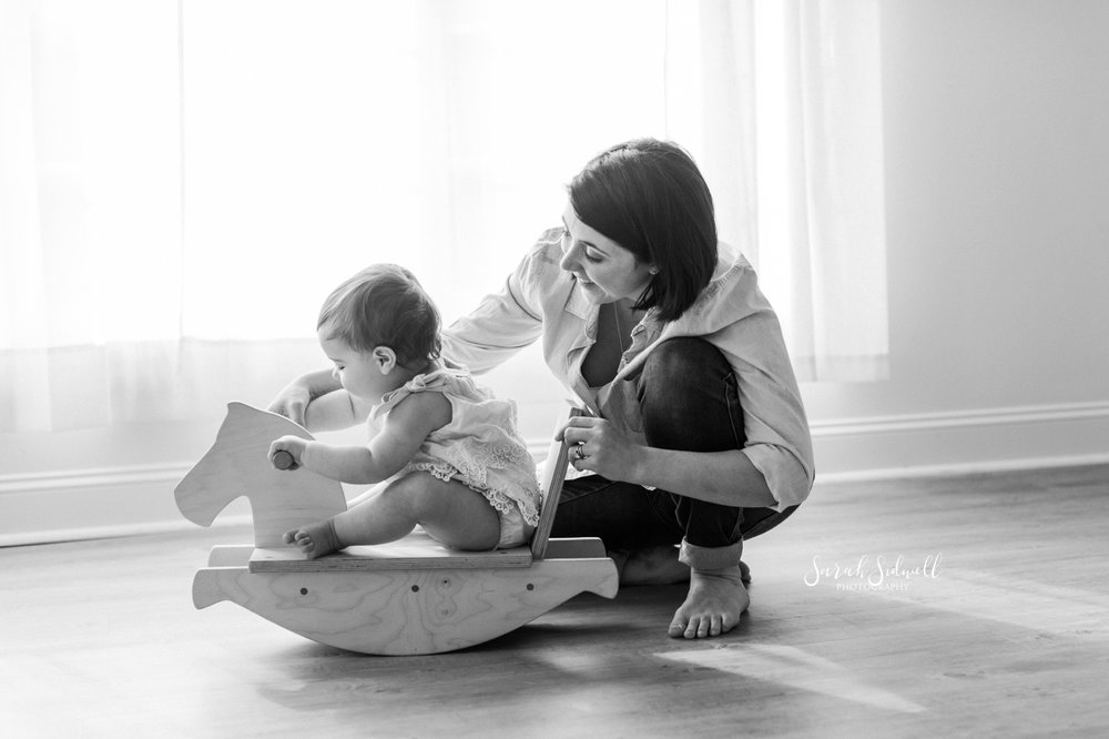 A baby plays on a rocking horse.
