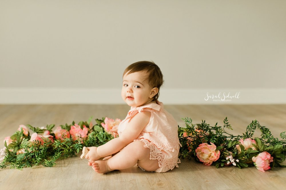 A baby sits in front of flowers | Nashville Baby Photographer