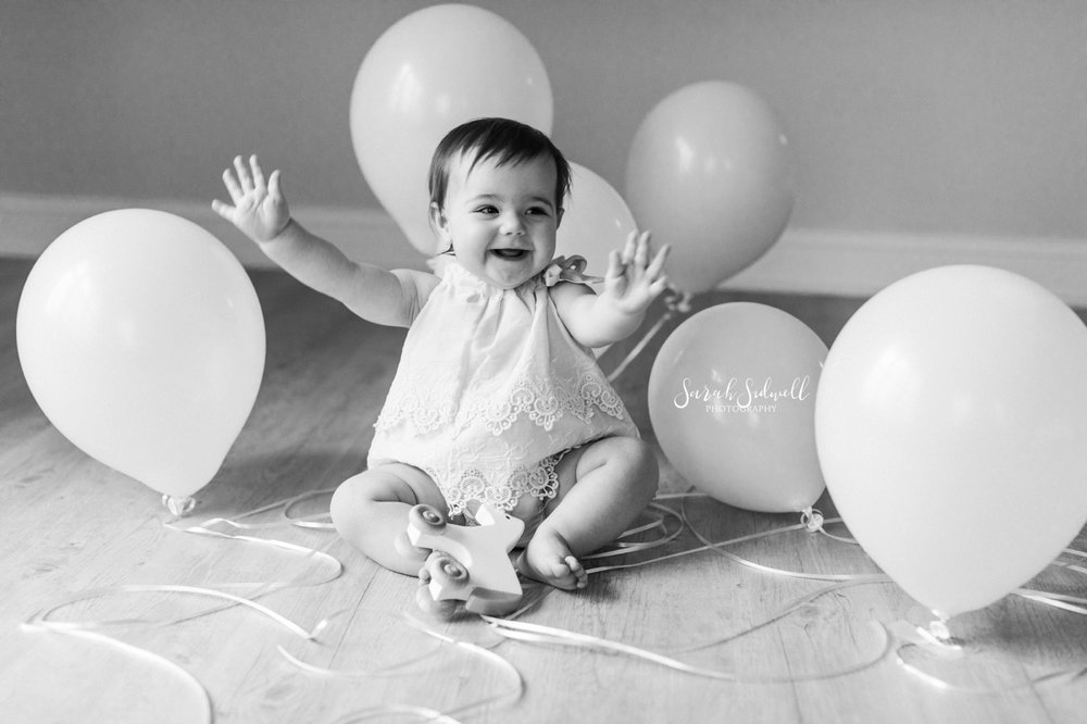 A baby pushes balloons out of her way.