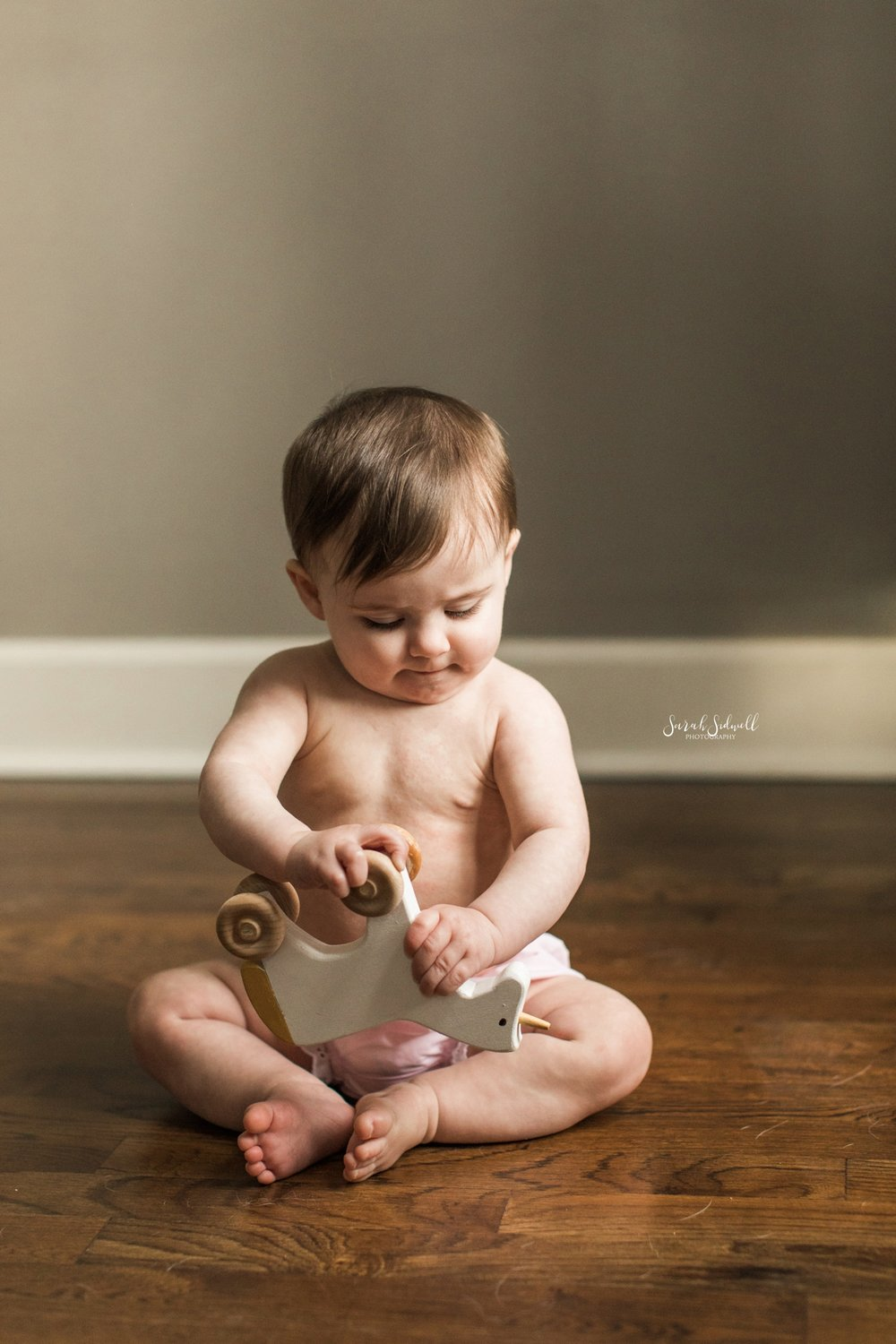 A baby sits up while playing.