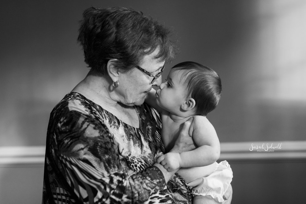 A grandma kisses her granddaughter.