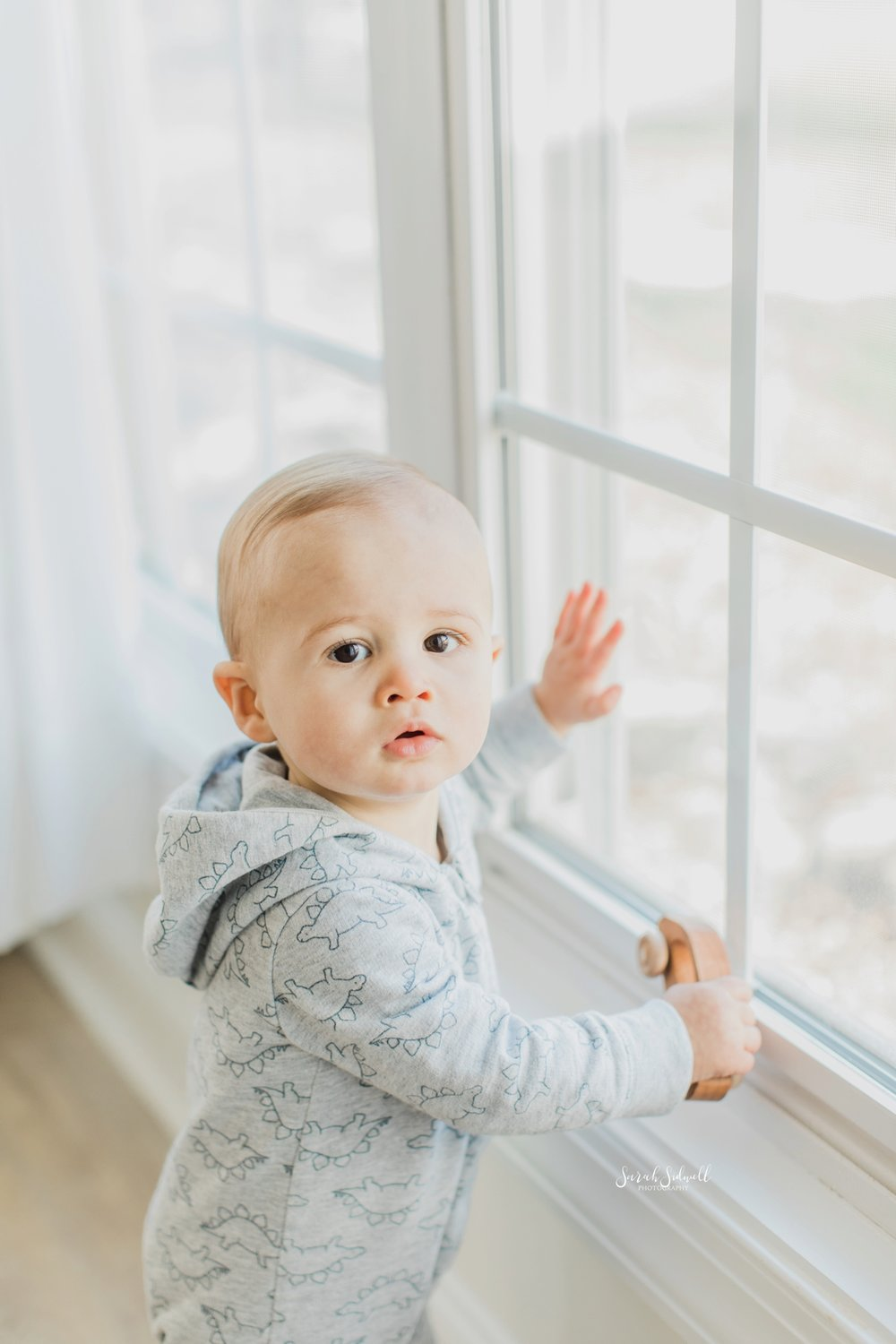 A baby wearing a blue jumper stands at a window and puts his hands up to it.