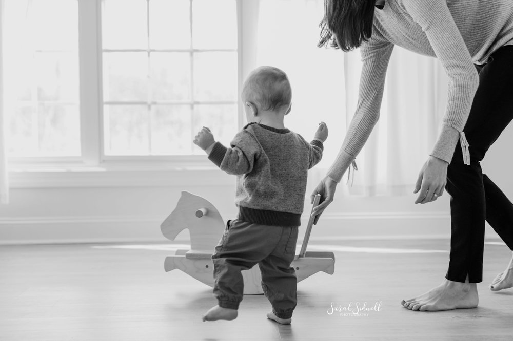A baby walks towards a wooden rocking horse.