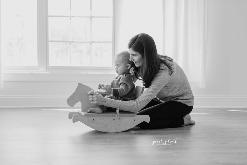 A baby rides a rocking horse | baby photography in Nashville.