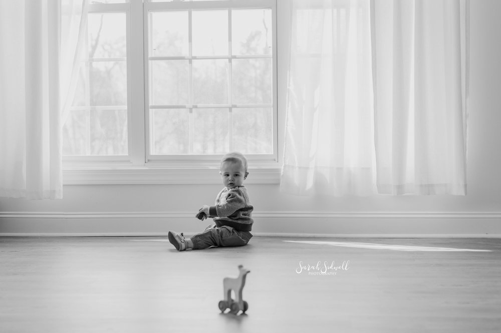 A baby sits on a hard floor near a big window.
