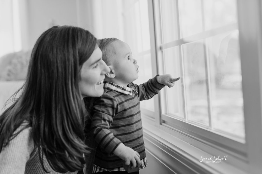 A mother stands behind her toddler, looking out of a big window.