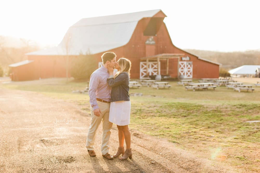 A couple embrace in the sunlight in front of a barn.