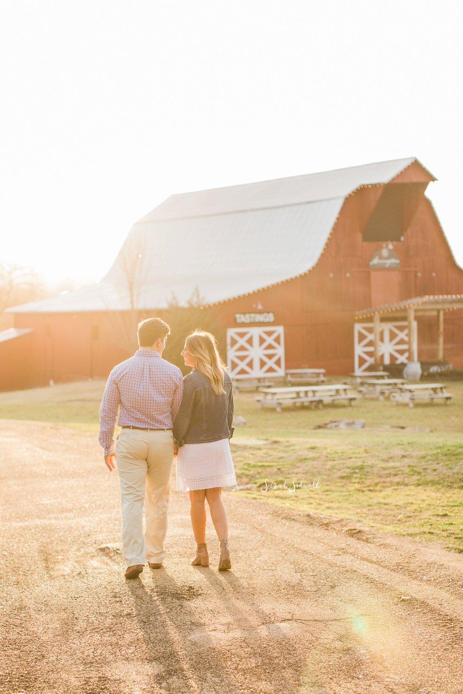 A couple walk in the sunlight towards a barn.