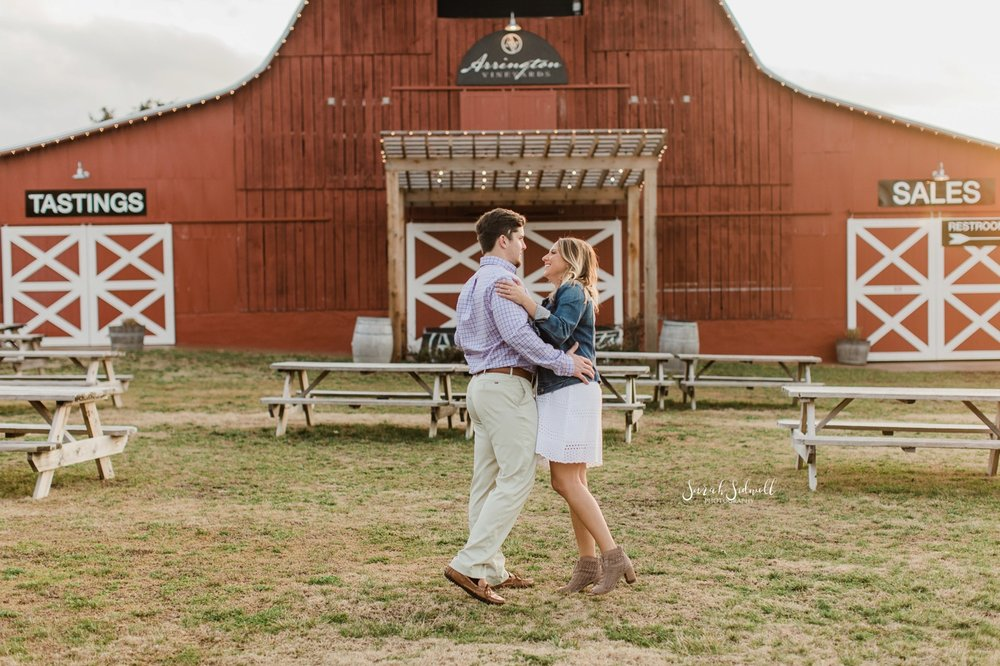 A couple kiss each other in front of a red barn.