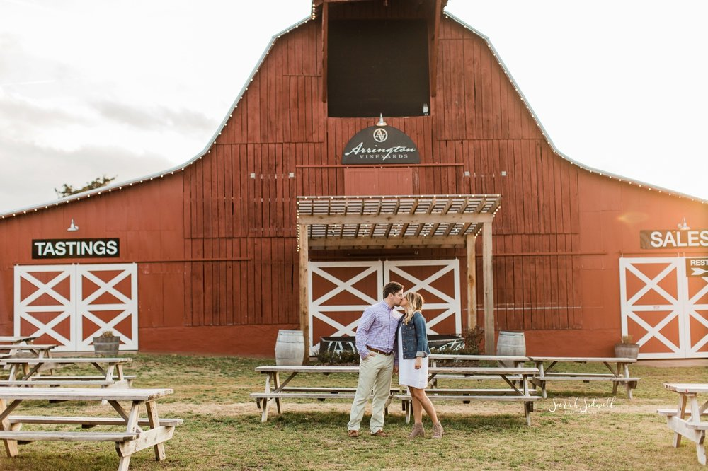 A couple stop to embrace in front of a barn at Arrington Vineyards.