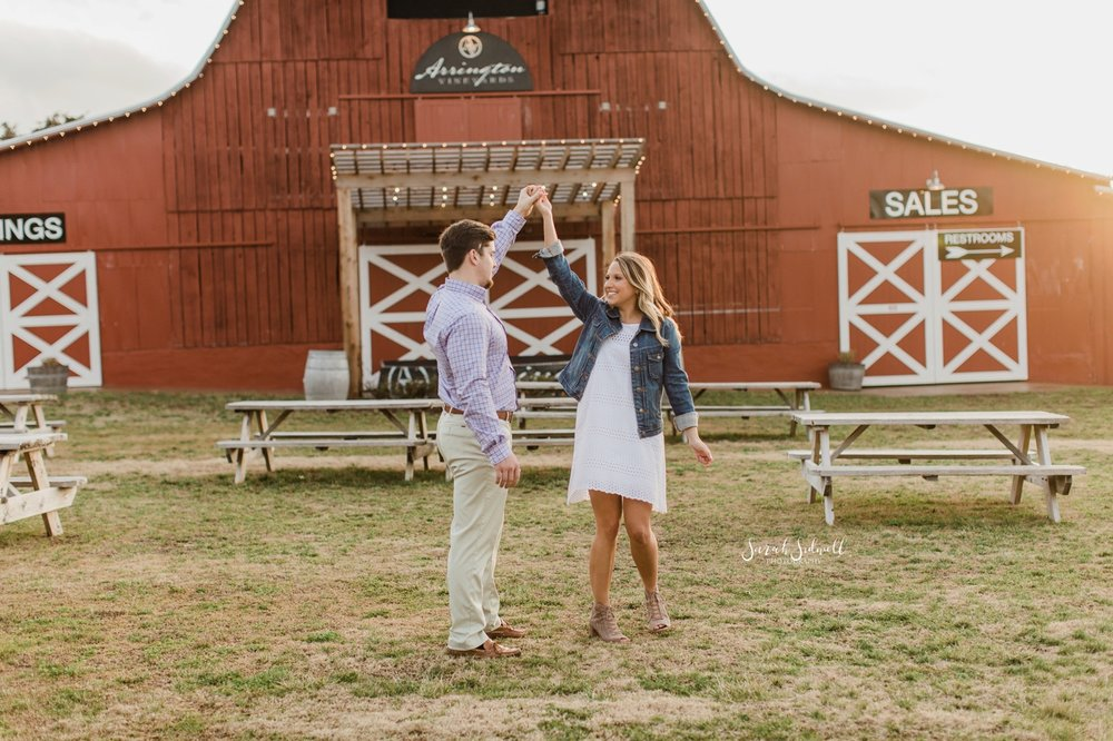 A man twirls his fiance in front of a red barn at Arrington Vineyards.