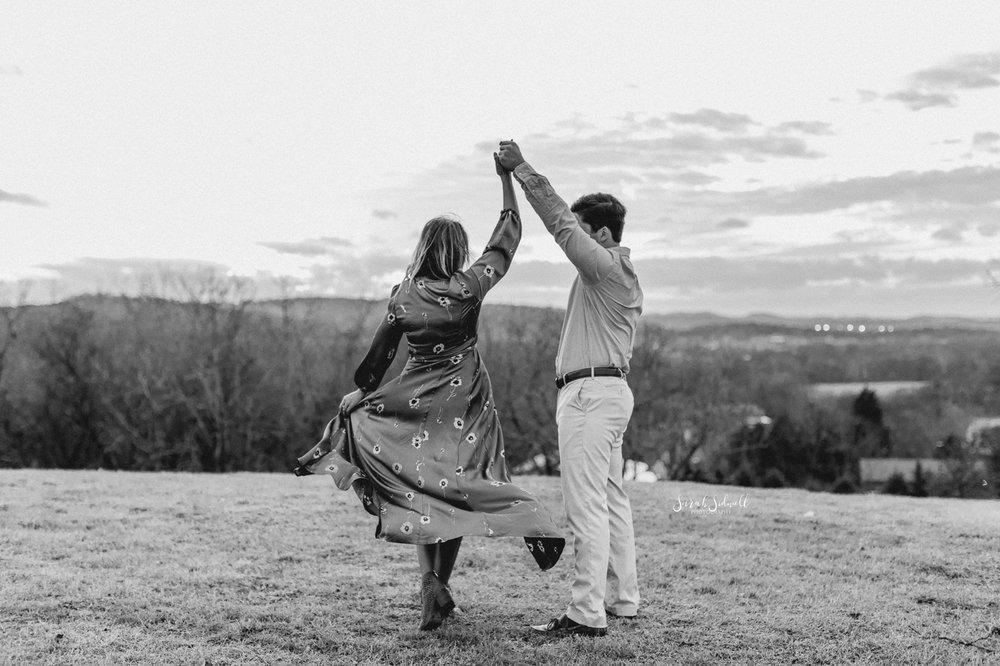 A man twirls his fiance as they dance in an open field.