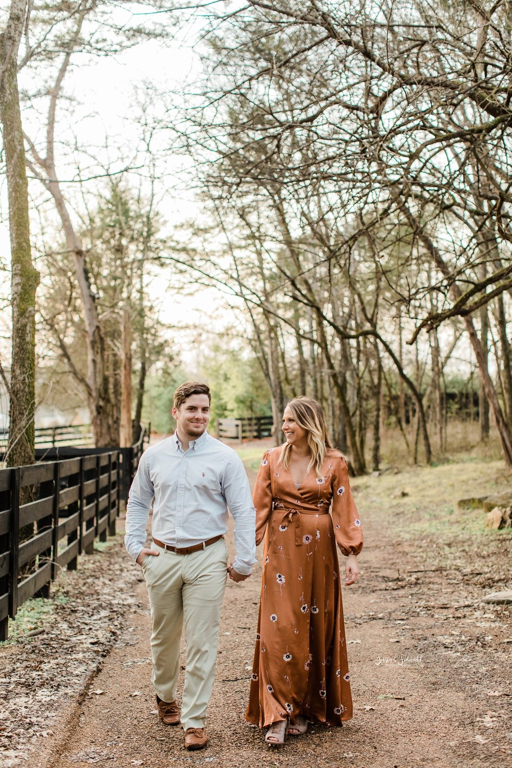 A couple are walking down a dirt path and enjoying a sunny day.