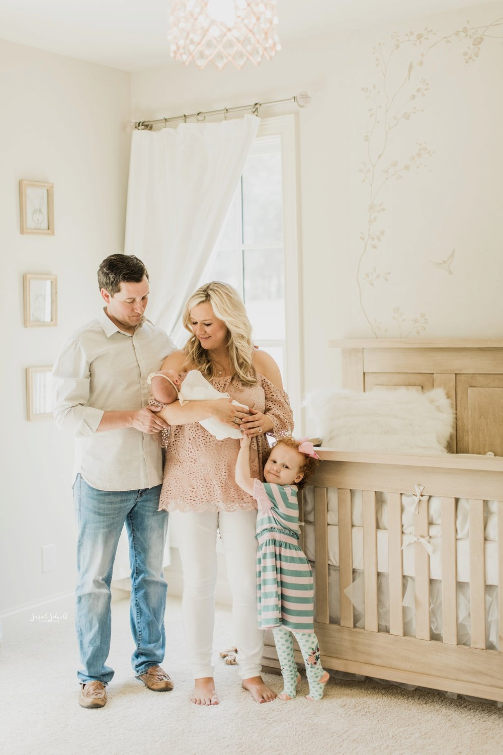 A family is standing in their baby's nursery | Home Newborn Session