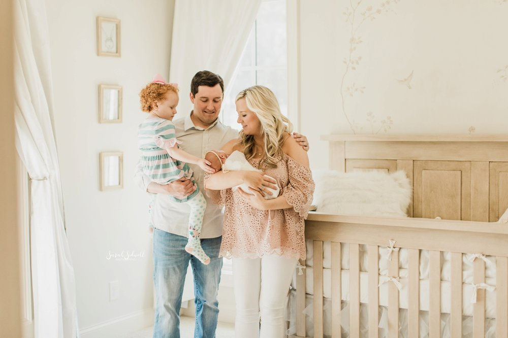 A family surrounds their newborn baby | Home Newborn Session