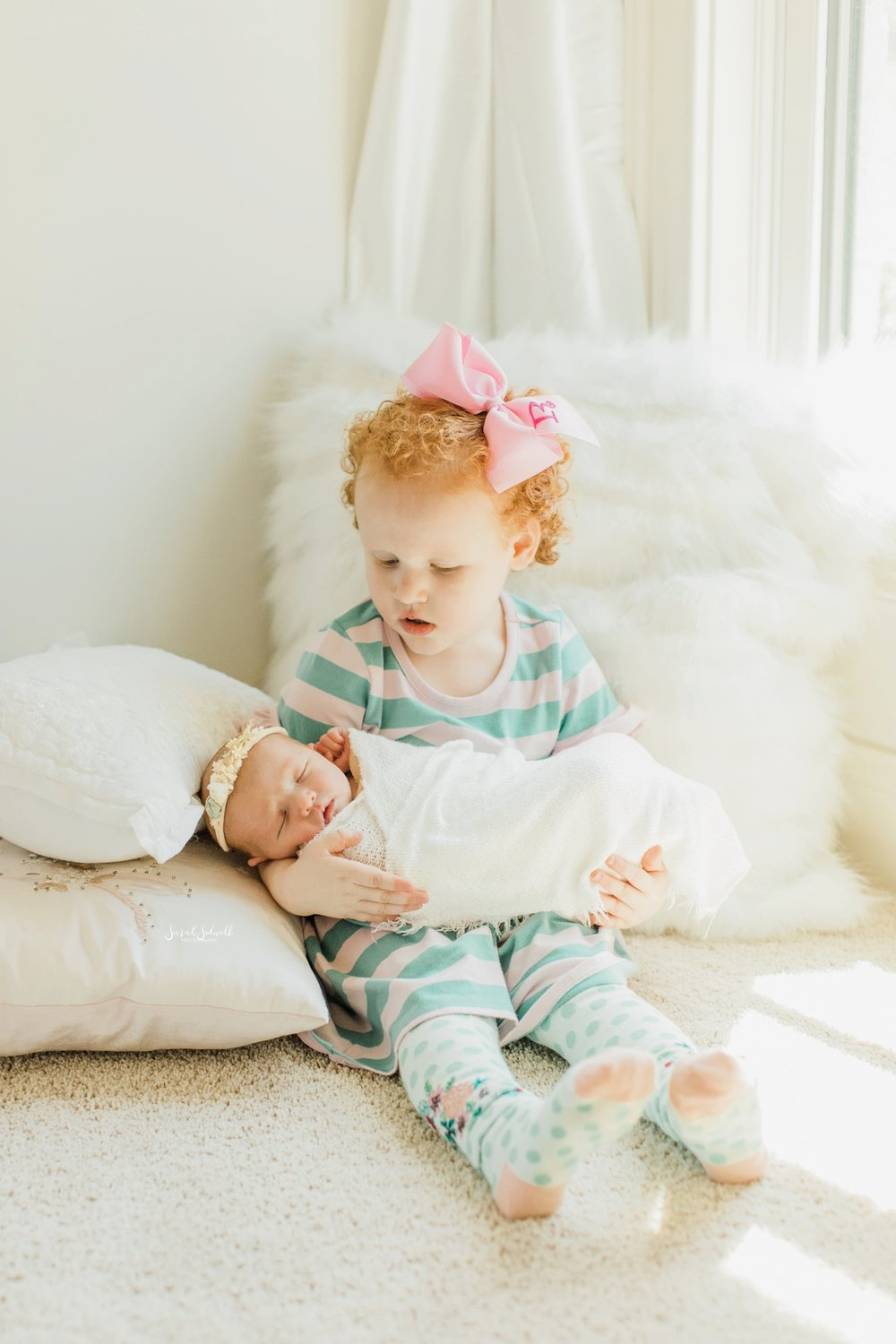A toddler holds her new baby sister | Home Newborn Session