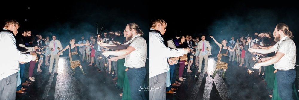 A wedding photographer walks through sparklers.