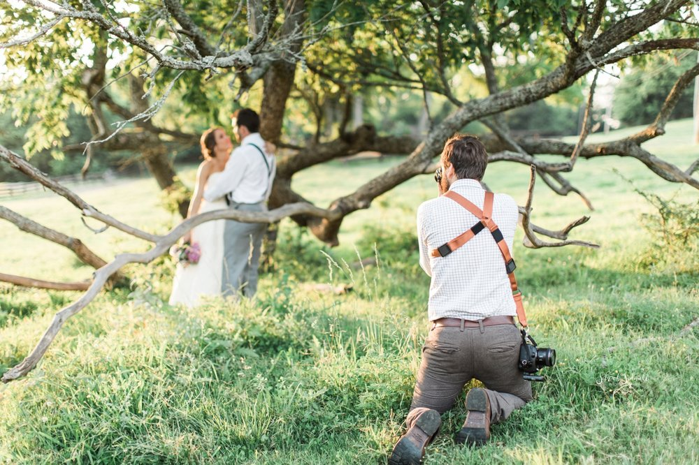 A man kneels down to get a good shot of a bridal couple.