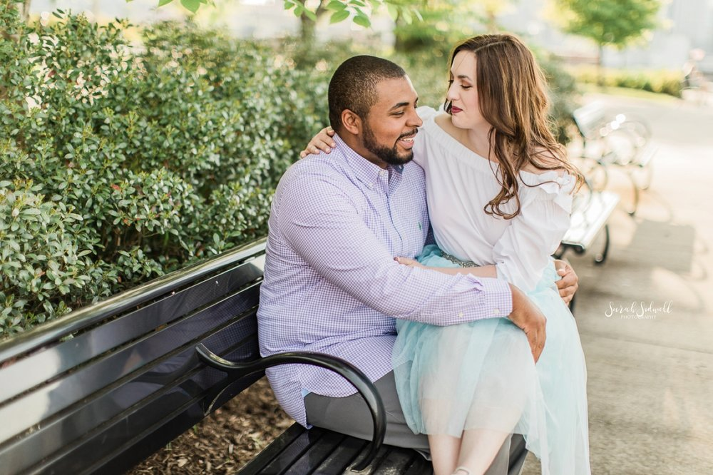 A woman sits on her fiance's lap on a park bench.