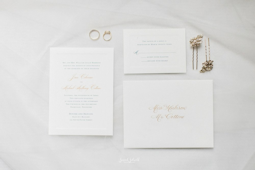 Wedding invitations are displayed on a white table.