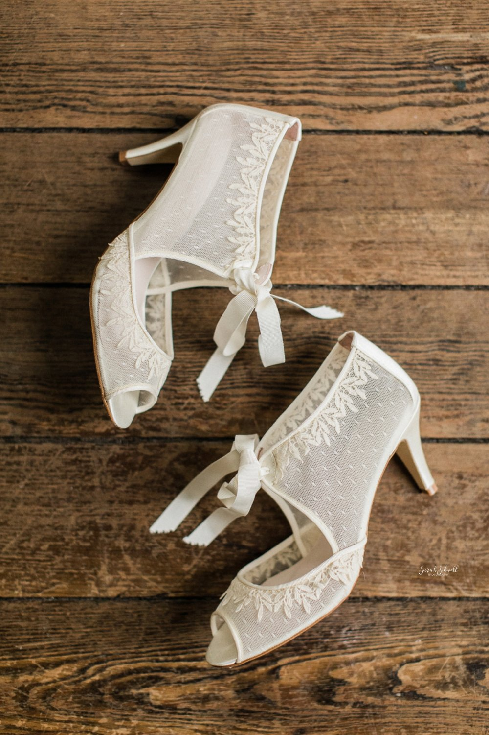 Bridal shoes lay on a wooden floor.