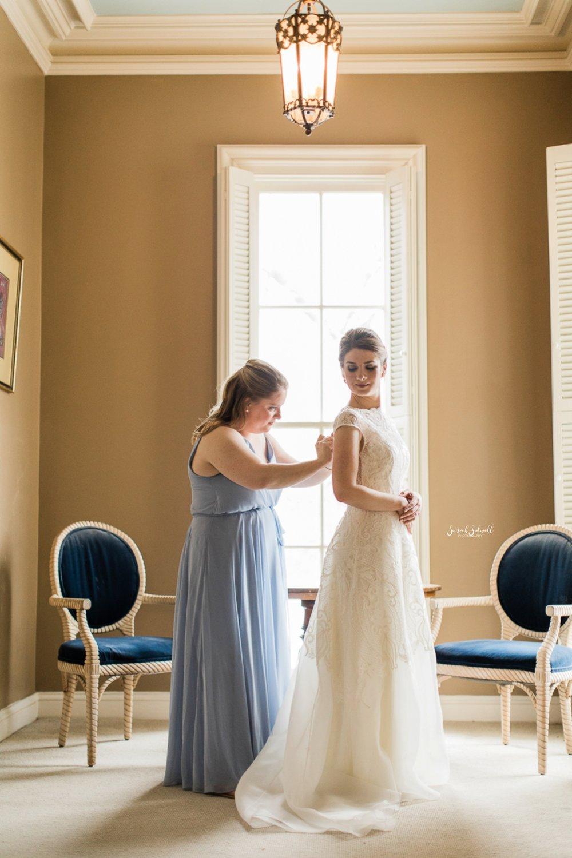 A bridesmaid helps a bride get ready.