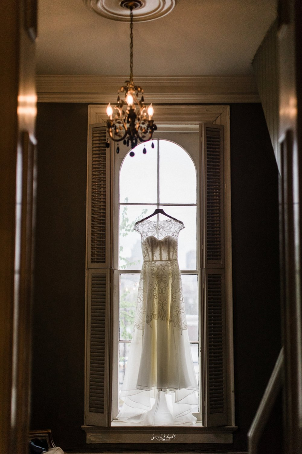 A wedding dress hangs in a window at the East Ivy Mansion.