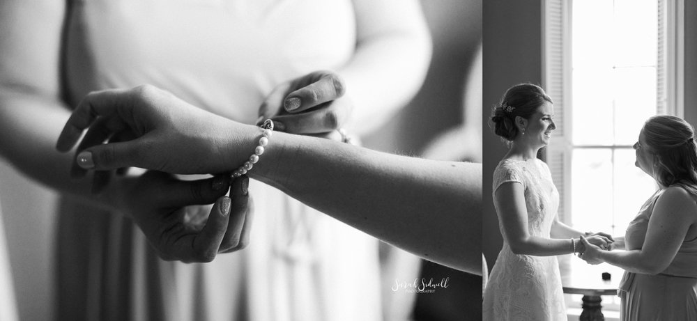 A woman buckles a bracelet onto a bride's wrist.
