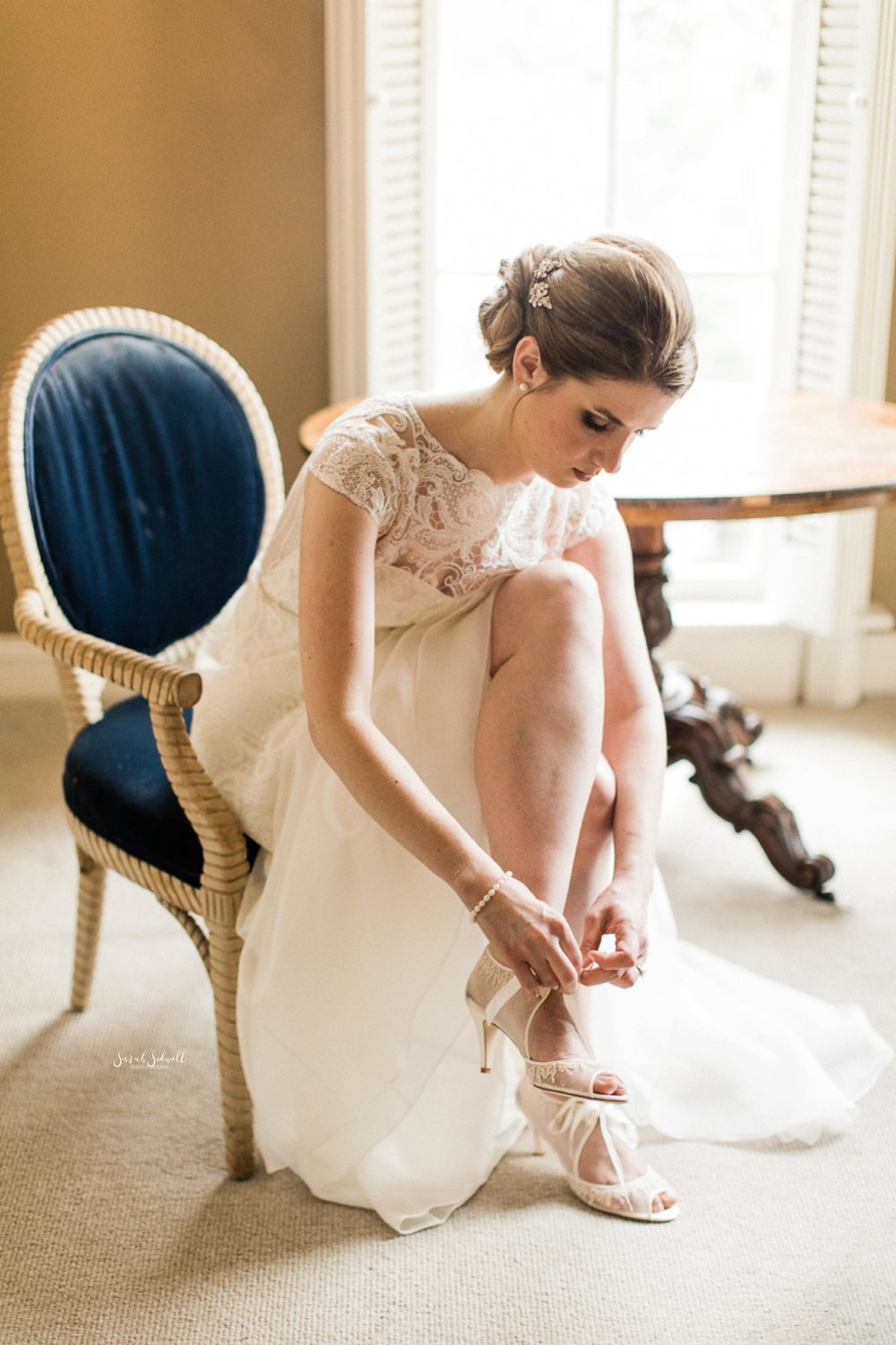 A bride sits to buckle her shoe.