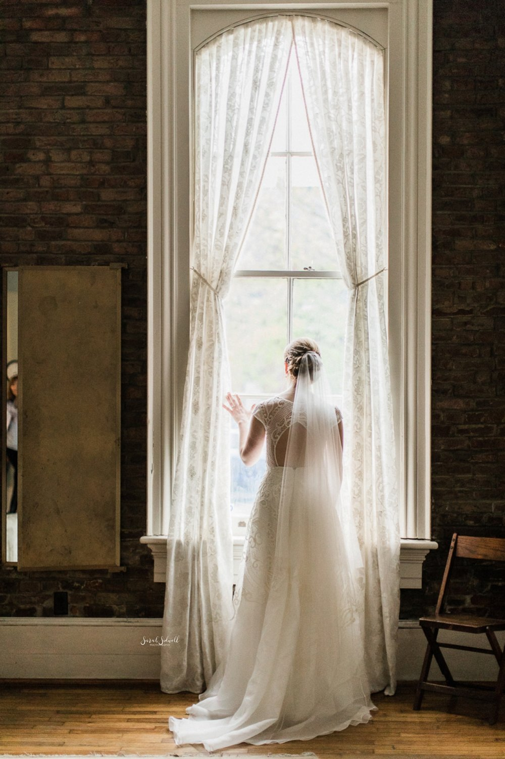A bride in a white dress stands looking out of a tall window.