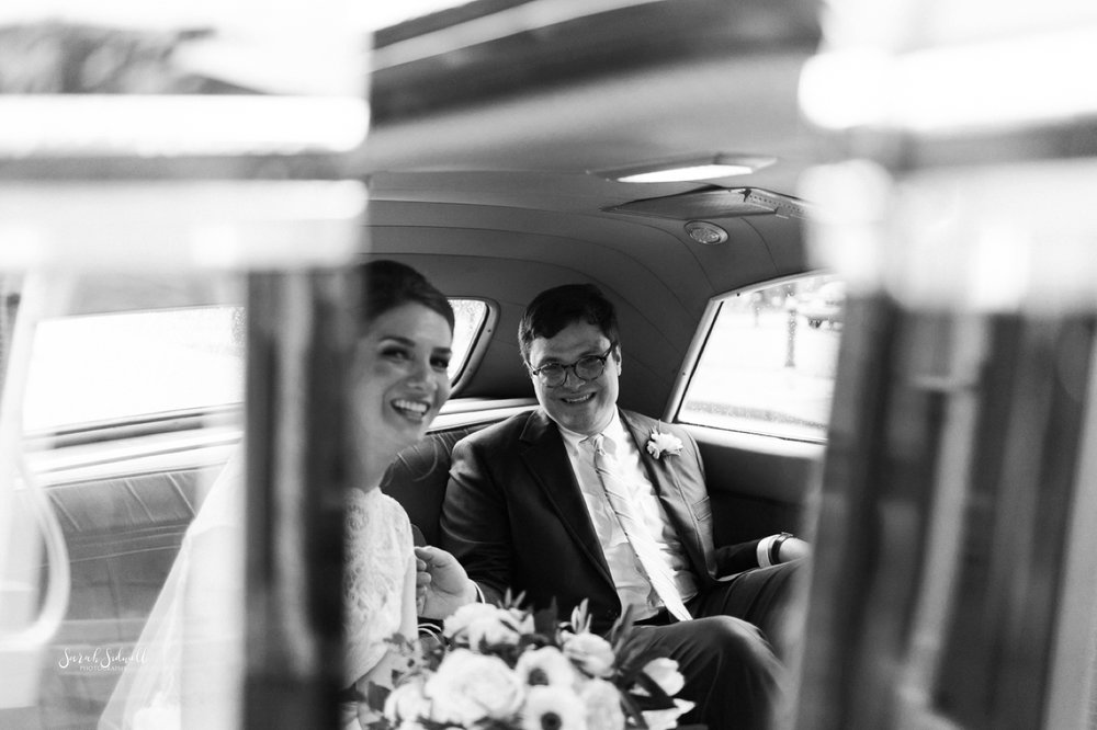 A bride and groom get into their get away car.
