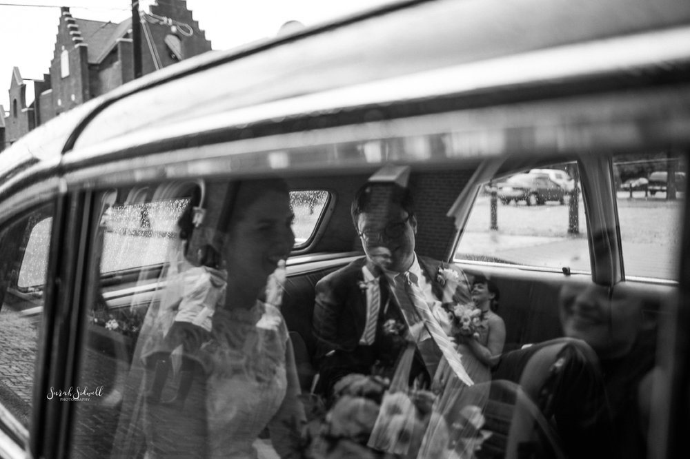 A bride and groom get into their ride after their ceremony.