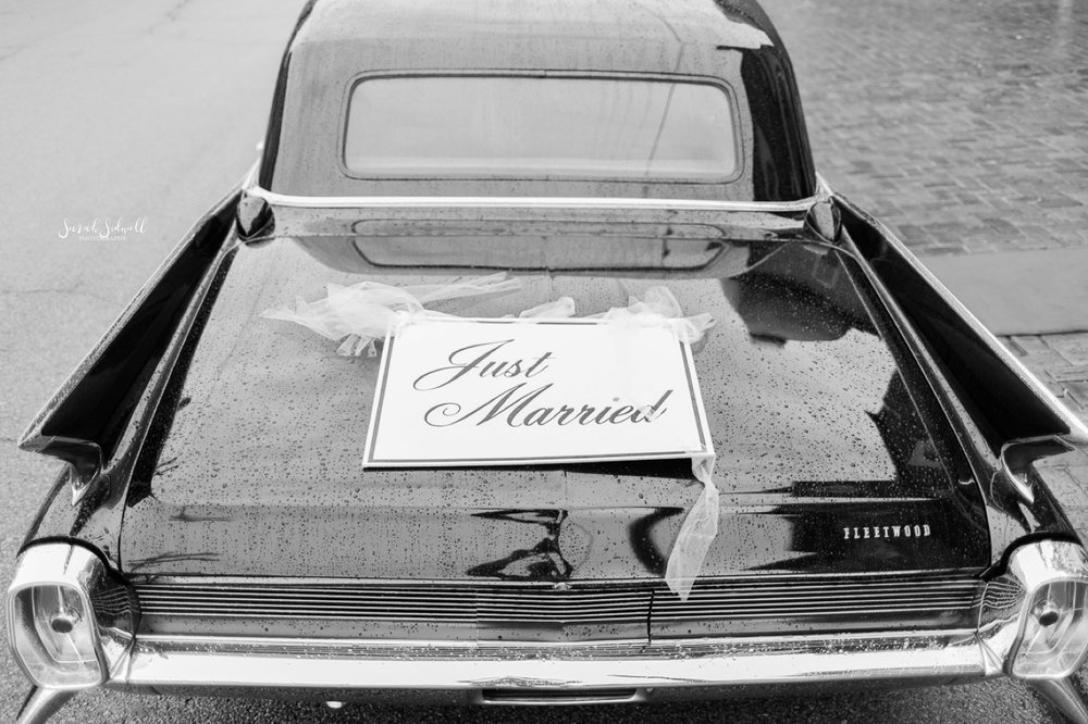 """A car has a """"just married"""" sign on the back of it."""