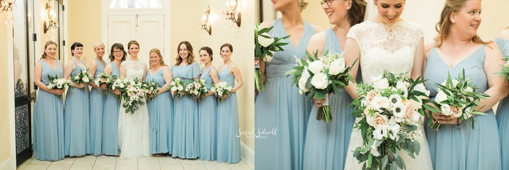 A bride stands with her bridesmaids who wear blue dresses.