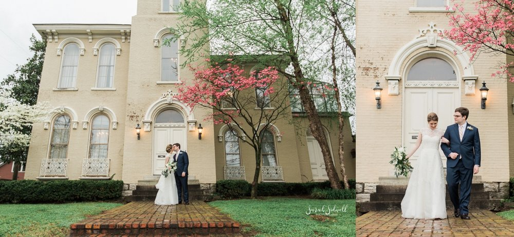 A bride and groom stand in front of the East Ivy Mansion.