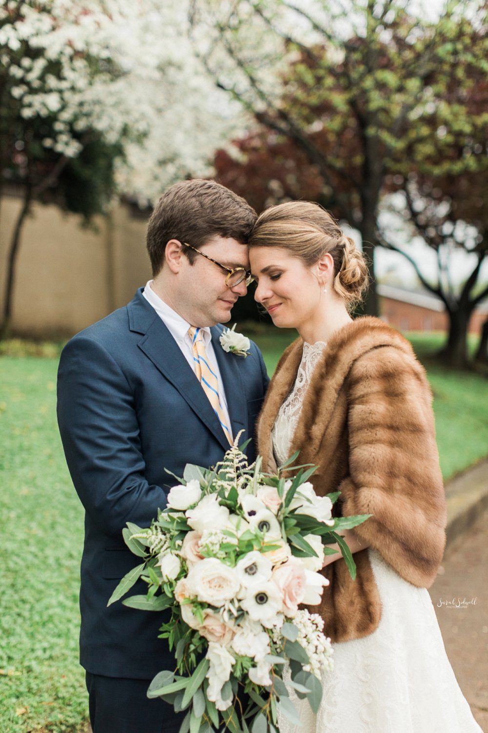 A bride wears a fur shawl while snuggling up to her husband.