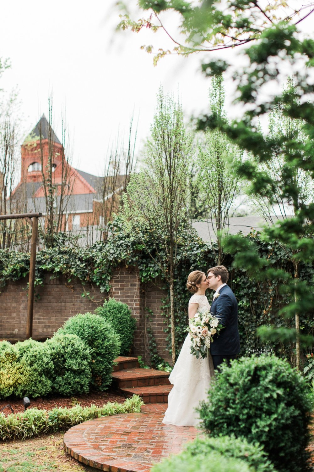A bride and groom steal a kiss in a secret garden.