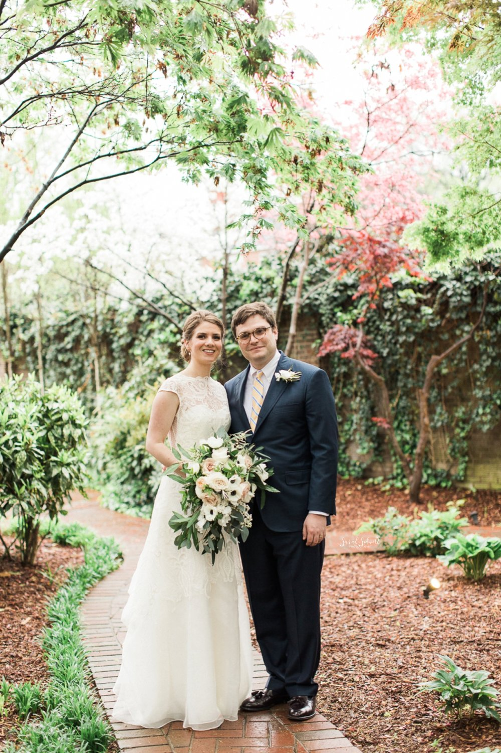 A bride and groom stand in a garden at the East Ivy Mansion