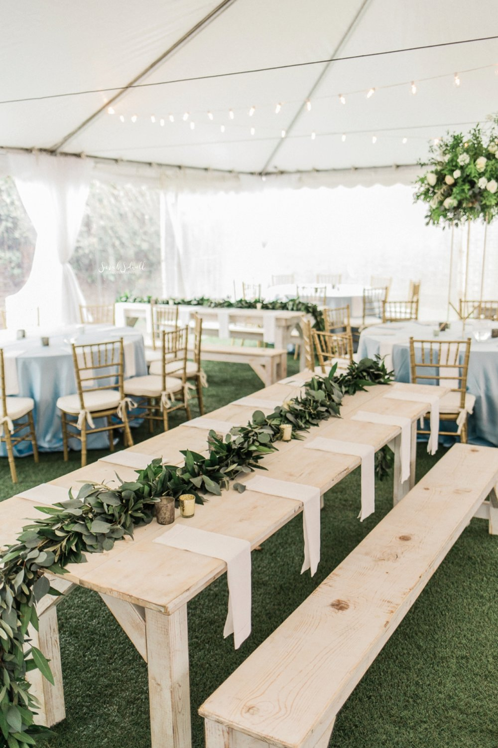A farmhouse table is decorated with greenery.