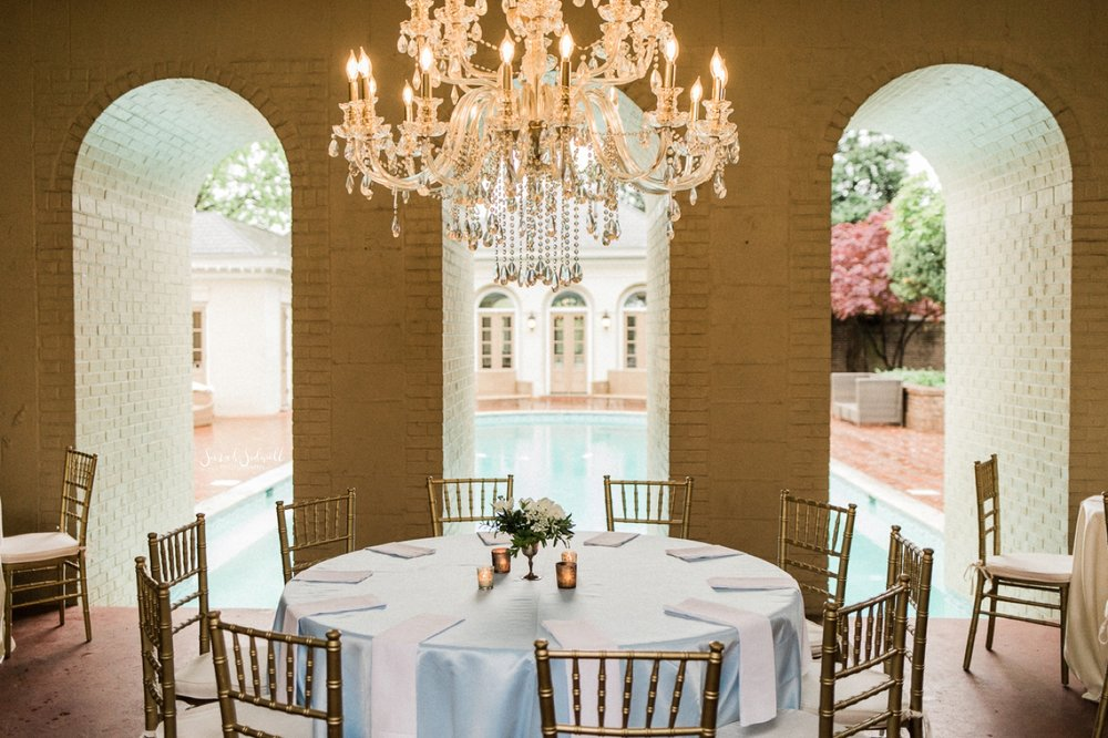 A venue has tables covered in white linen for a wedding reception.