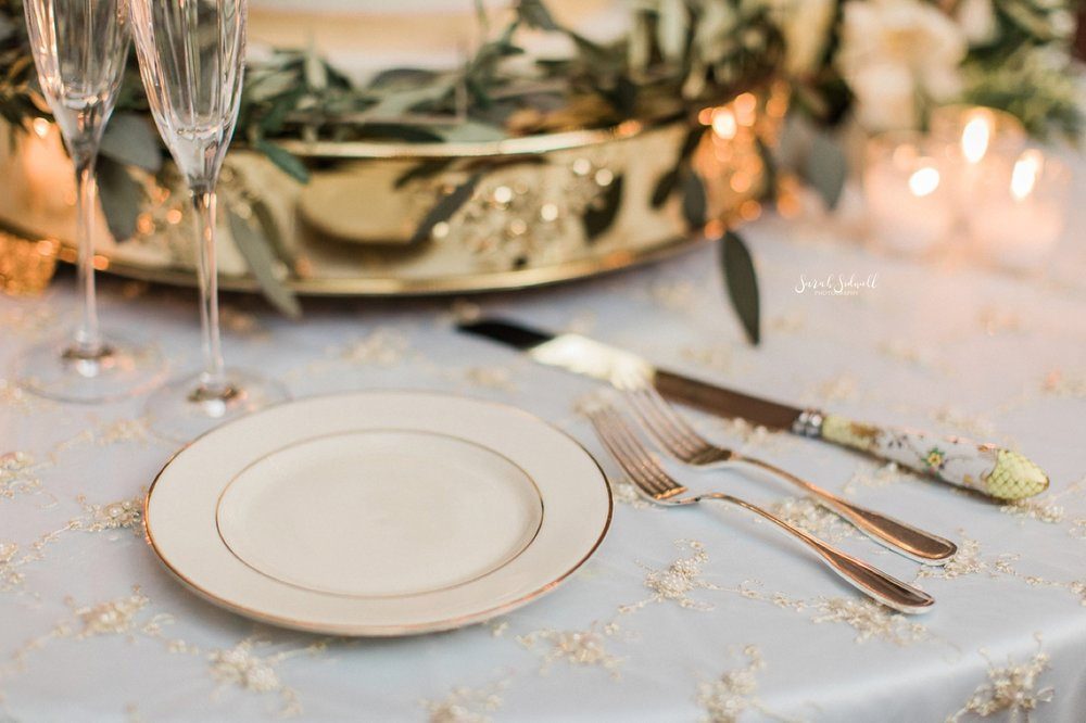 Ivory plates with golden trim are used for a wedding reception.