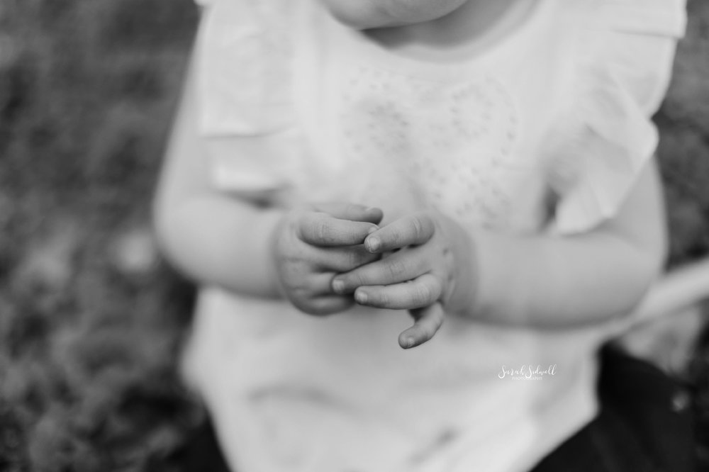 A toddler with chubby fingers plays with her hands.