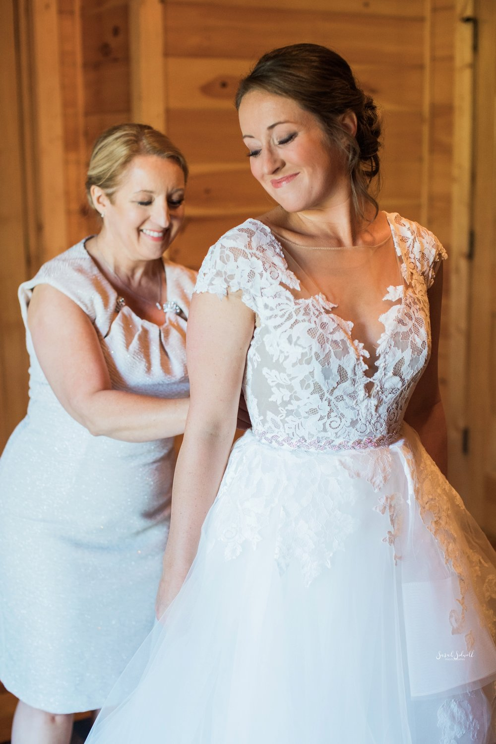 A bride gets help fastening her dress.
