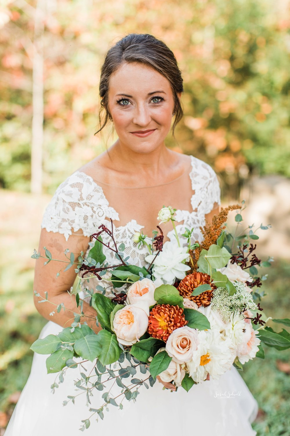 A bride holds her bouquet and smiles at the camera.