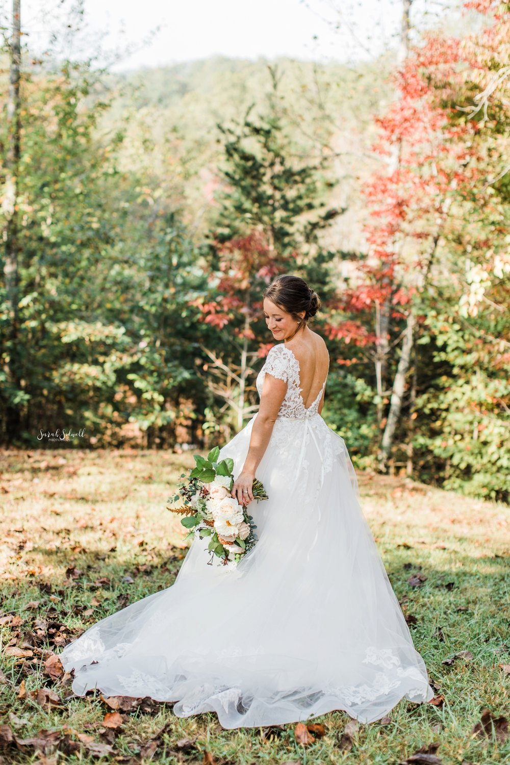 A bride wearing a white dress stands among wild flowers.
