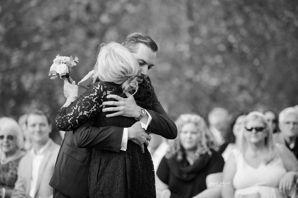 A groom hugs his mom before his wedding.